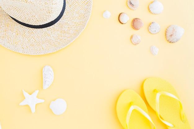 Composizione di accessori per vacanze esotiche in spiaggia su sfondo giallo