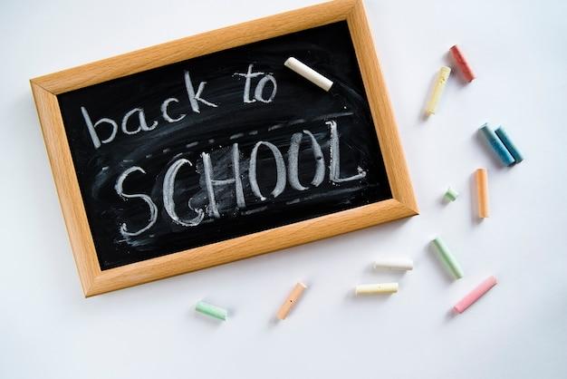 Composizione di back to school, nota a bordo e gessetti