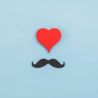 Composizione di baffi neri e cuore rosso