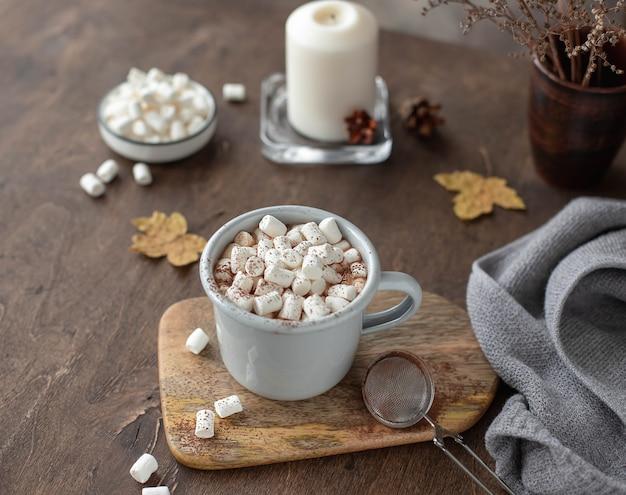 Composizione di cacao con caramelle gommosa e molle in una tazza su un tavolo di legno. buio