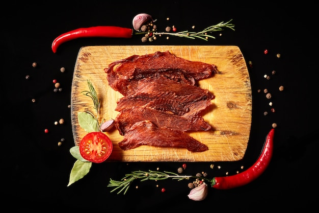 Composizione di carne secca con spezie, peperoncino e rosmarino su una tavola di cucina su uno sfondo nero