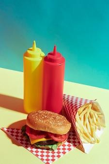 Composizione di cibo ad alto angolo con bottiglie di salsa e hamburger