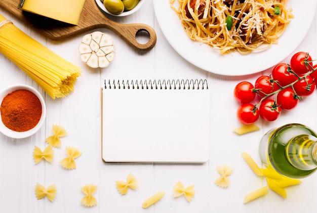 Composizione di cibo italiano piatto laici con modello di blocco note