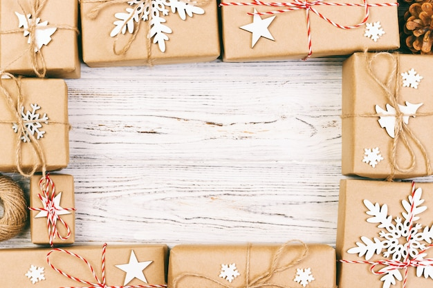 Composizione di cornice di natale e capodanno. confezioni regalo di natale avvolto a mano con decorazione su bianco con copyspace vuoto per il testo. sopra la vista, disteso. tonica
