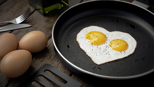 Composizione di cottura, uovo a forma di cuore con due tuorli in padella.