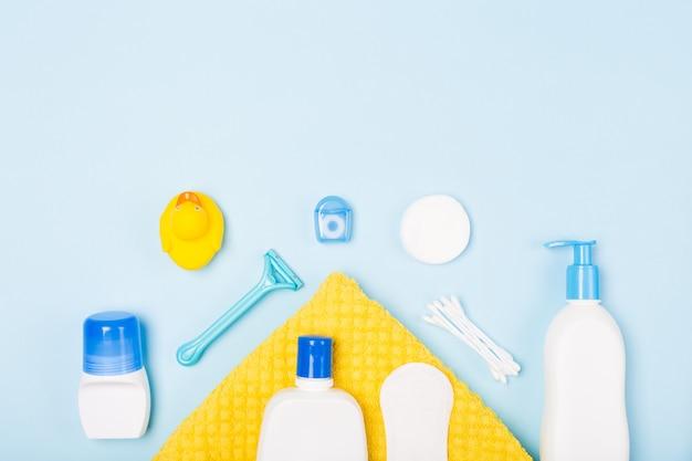 Composizione di disposizione piana regolare di vista superiore di mattina di cura di pulizia del fronte del bagno della donna con gli oggetti bianchi e blu sullo scrittorio blu-chiaro