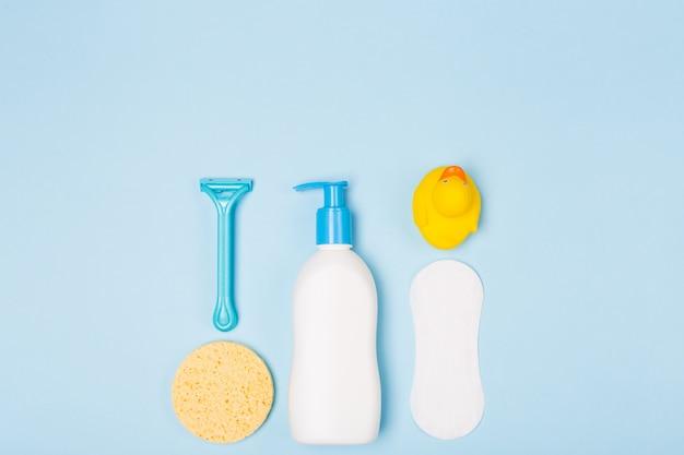 Composizione di disposizione piana sistemata di vista superiore di mattina di cura di pulizia del bagno della donna con gli oggetti bianchi e blu sullo scrittorio blu-chiaro