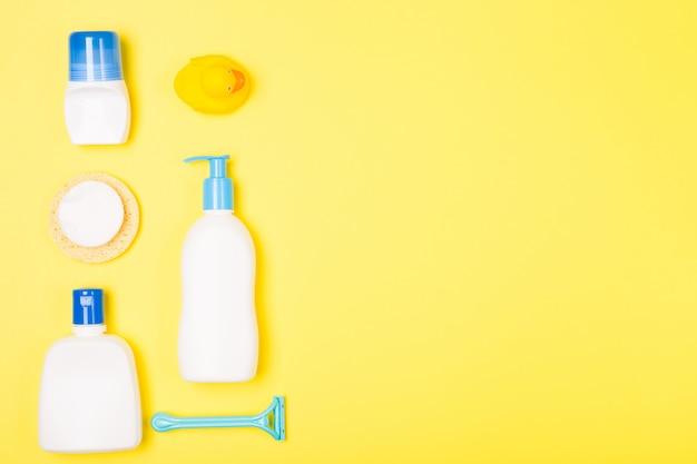 Composizione di disposizione piana sistemata di vista superiore di mattina di cura di pulizia del bagno della donna con gli oggetti gialli bianchi e blu sullo scrittorio giallo.