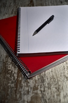 Composizione di due quaderni e una penna a sfera su un legno