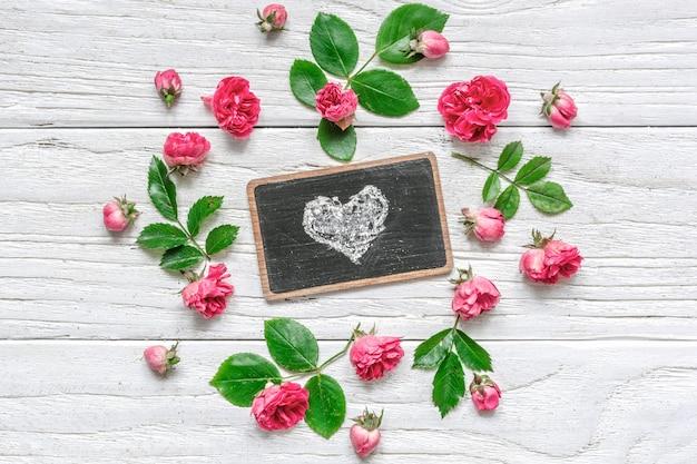 Composizione di fiori. cornice fatta di fiori rosa rosa con il simbolo del cuore sulla lavagna