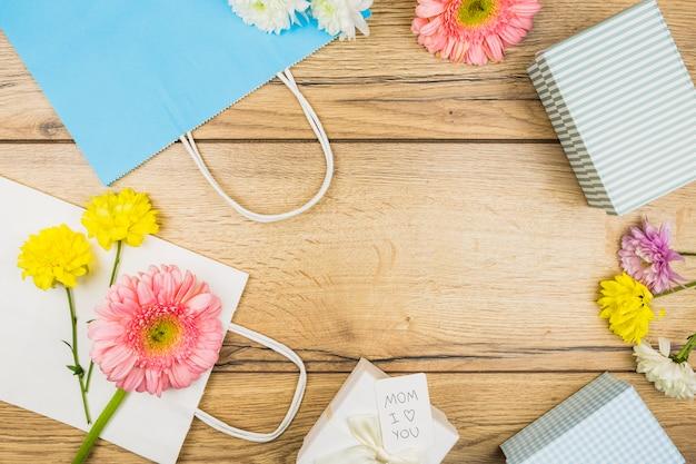 Composizione di fiori freschi, scatole presenti e pacchetti di carta