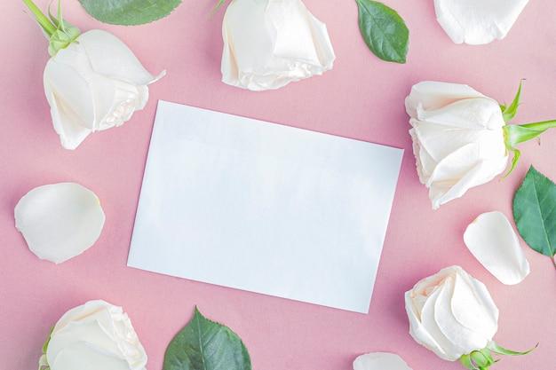 Composizione di fiori piatti per le tue scritte. cornice fatta di fiori rosa bianchi su sfondo rosa. biglietto di auguri.