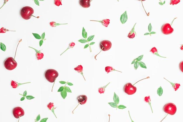 Composizione di fiori rossi, ciliegie e foglie verdi