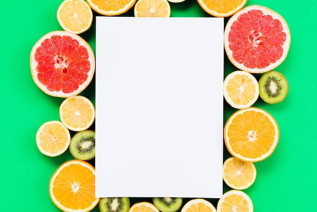 Composizione di frutta esotica colorata a fette con carta bianca