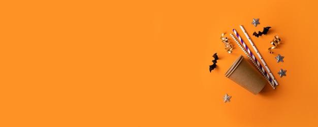 Composizione di halloween di bicchieri di carta, tubuli multicolori per bevande, pipistrelli di carta nera, stelle