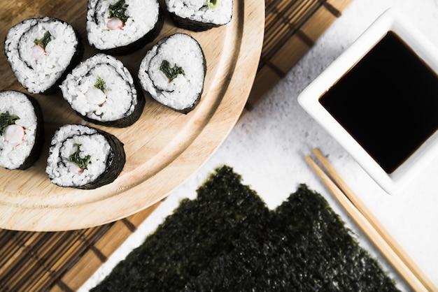 Composizione di involtini di sushi con salsa e bacchette