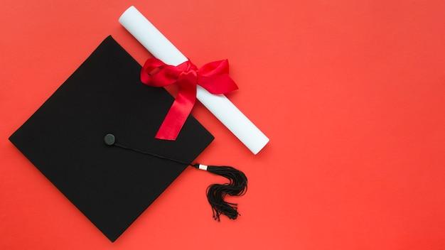 Composizione di laurea festiva con cappello accademico e diploma
