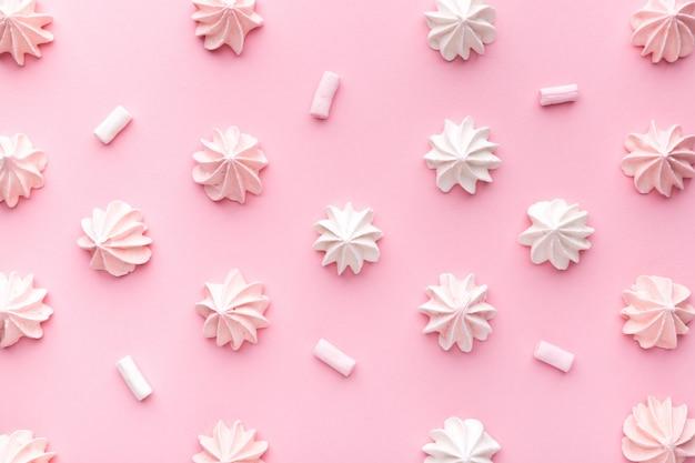 Composizione di meringhe rosa e bianche su una carta rosa. pastello.