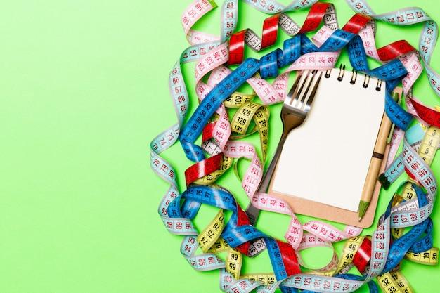 Composizione di nastri di misurazione colorati, forchetta, penna e blocco note su sfondo verde. vista dall'alto del controllo della dieta e spazio vuoto per la progettazione