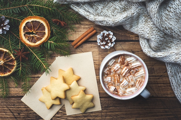 Composizione di natale, biscotti al cioccolato caldo, rami di pino, bastoncini di cannella, stelle di anice.