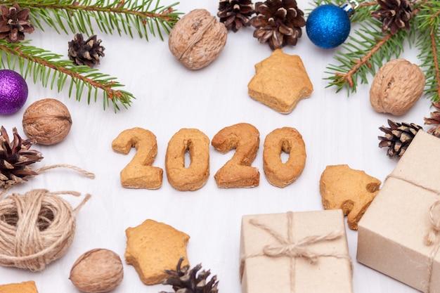 Composizione di natale. biscotti di panpepato di natale, biscotti a forma di numeri 2020, rami di abete, regali. nuovo anno 2020. vista piana, vista dall'alto.