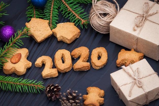 Composizione di natale. biscotti di panpepato di natale, biscotti a forma di numeri 2020, rami di abete, regali. nuovo anno 2020.