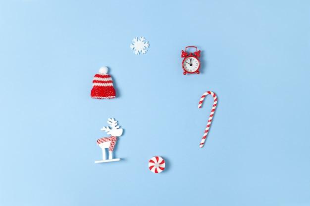 Composizione di natale con bastoncino di zucchero, cervo, cappello, fiocco di neve e orologio rosso