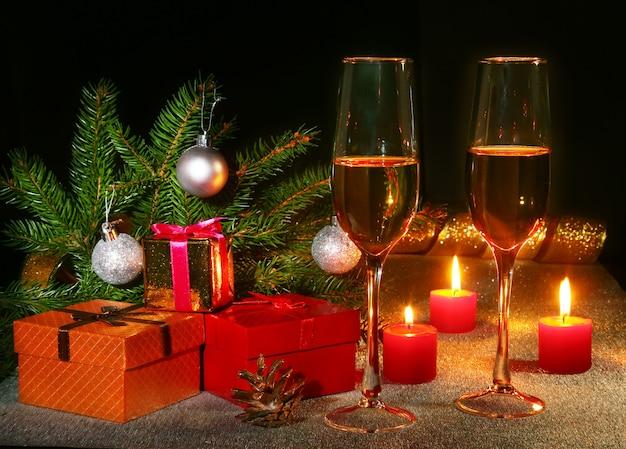 Composizione di natale con bicchiere di spumante champagne o cognac, candele natalizie, palline colorate, confezione regalo e albero su una decorazione scintillante di capodanno.