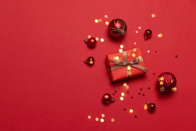 Composizione di natale con confezione regalo di carta rossa, nastro, caramelle e diverse dimensioni palle di natale su uno sfondo rosso.