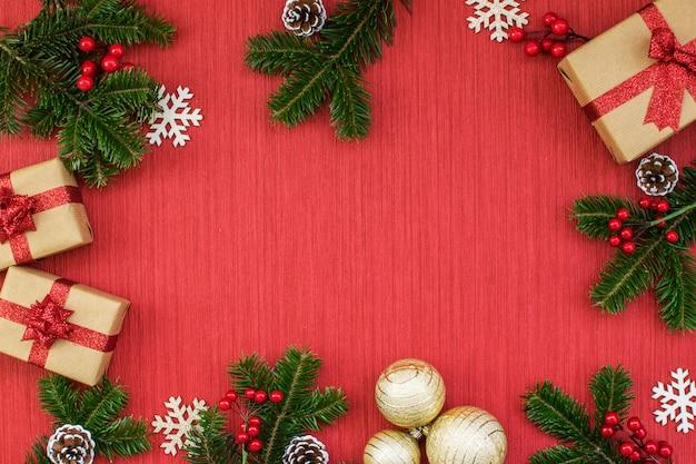 Composizione di natale con doni, palline d'oro, pigne, rami di abete, vischio e fiocchi di neve su uno sfondo rosso