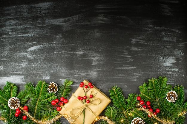 Composizione di natale con doni, tinsel dorato, pigne, rami di abete, vischio e luci di natale su sfondo scuro