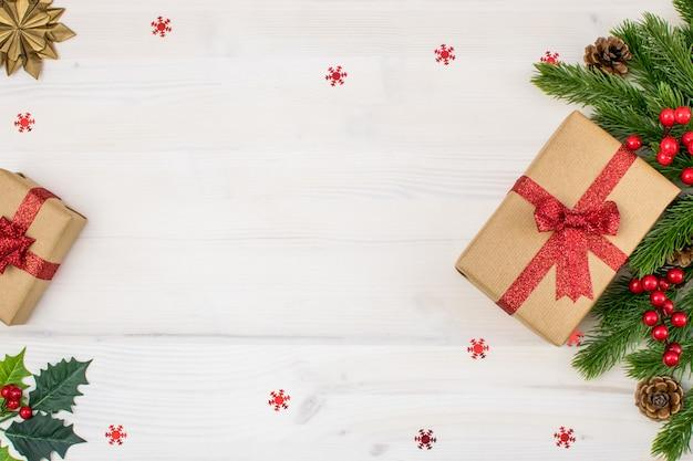 Composizione di natale con doni, vischio, pigne, rami di abete e fiocchi di neve su uno sfondo di legno chiaro