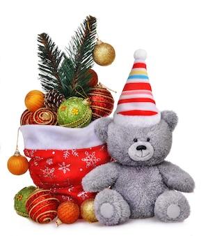Composizione di natale con la borsa di babbo natale piena di giocattoli e orsacchiotto sorridente