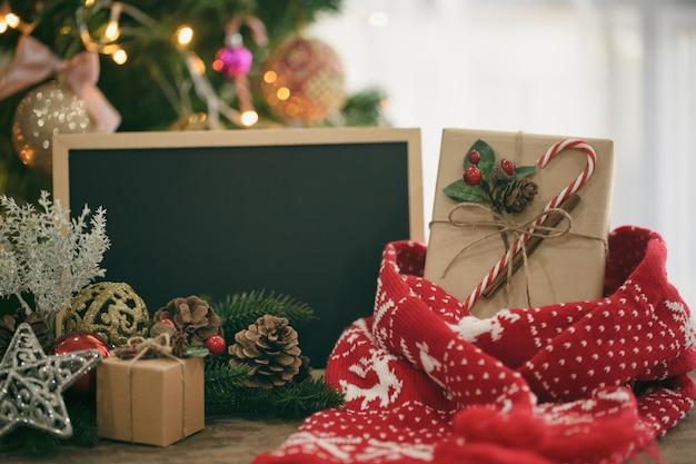 Composizione di natale con lanterna, foglie, pigne, confezione regalo, sciarpa rossa e lavagna