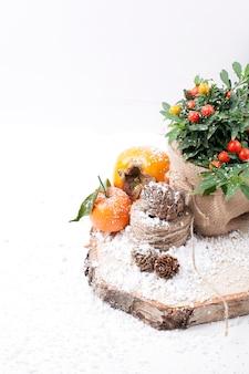 Composizione di natale con neve e frutta