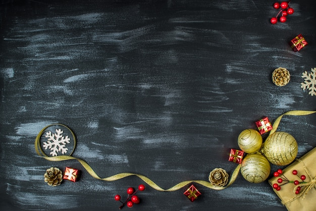 Composizione di natale con palle di natale, regali, pigne, vischio, fiocchi di neve, bastoncino di zucchero su sfondo scuro