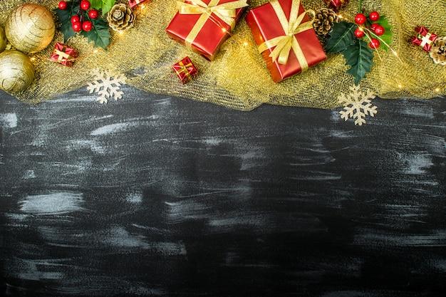 Composizione di natale con palle di natale, regali, pigne, vischio, fiocchi di neve su uno sfondo scuro con texture