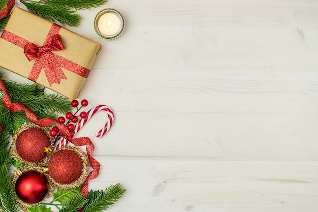 Composizione di natale con palle di natale, regali, vischio, candela, rami di abete e fiocchi di neve su uno sfondo di legno chiaro.