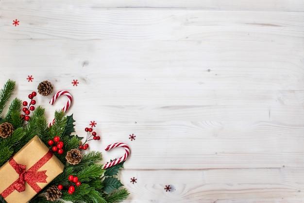 Composizione di natale con rami di abete, caramelle, regali, pigne e stelle su legno chiaro