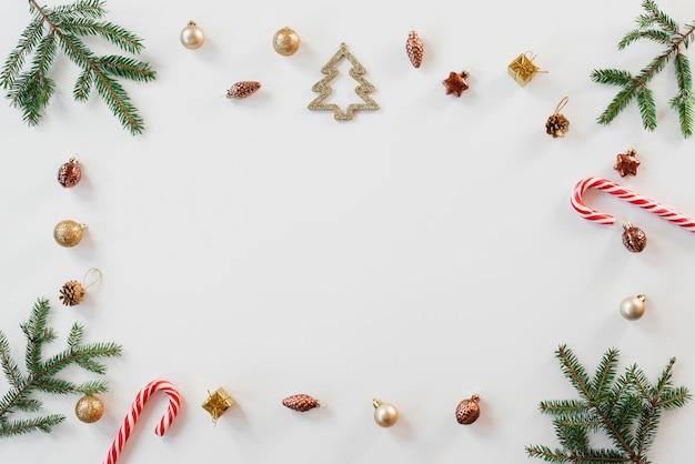 Composizione di natale con rami di abete, elementi in oro e bastoncino di zucchero