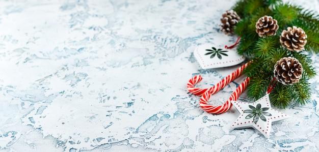 Composizione di natale con ramo di abete, decorazioni natalizie, bastoncini di zucchero