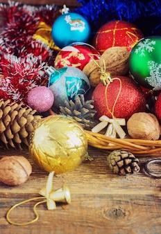 Composizione di natale con regali. basket, palline rosse, pigne, fiocchi di neve sul tavolo di legno. stile vintage