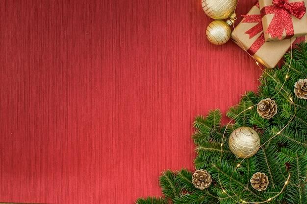 Composizione di natale con regali, palline d'oro, pigne, rami di abete, luci su uno sfondo rosso