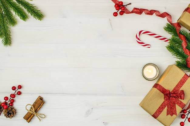Composizione di natale con regali, vischio, pigne, nastro rosso, rami di abete e fiocchi di neve su uno sfondo di legno chiaro