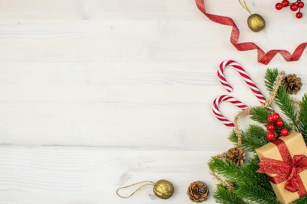 Composizione di natale con regali, vischio, pigne, rami di abete, bastoncino di zucchero, tinsel e fiocchi di neve su uno sfondo di legno chiaro