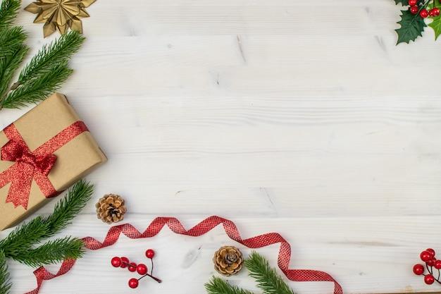 Composizione di natale con regali, vischio, pigne, rami di abete, nastro rosso e fiocchi di neve su uno sfondo di legno chiaro