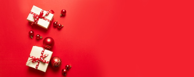 Composizione di natale con scatole di artigianato rosso festivo e nastri rossi e palline su rosso.