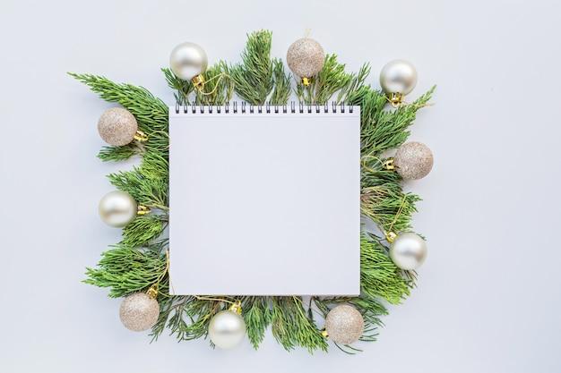 Composizione di natale con spazio in bianco di carta, bagattelle, rami di abete su bianco. concetto di nuovo anno.