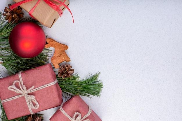 Composizione di natale. decorazioni bianche di natale, rami di abete con i contenitori di regalo dei giocattoli su priorità bassa bianca.