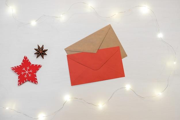 Composizione di natale decorazioni rosse con busta della lettera su sfondo bianco.